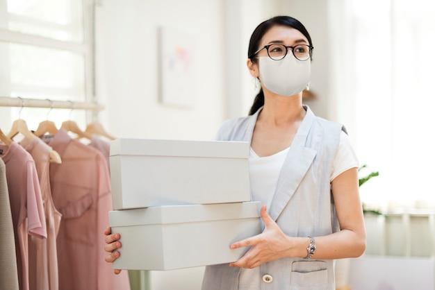 Mitarbeiterin in der neuen normalen maske mit schuhkartons