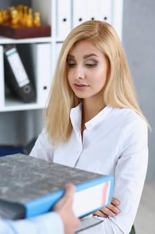 Mitarbeiterin zeigt packung mit dokumenten