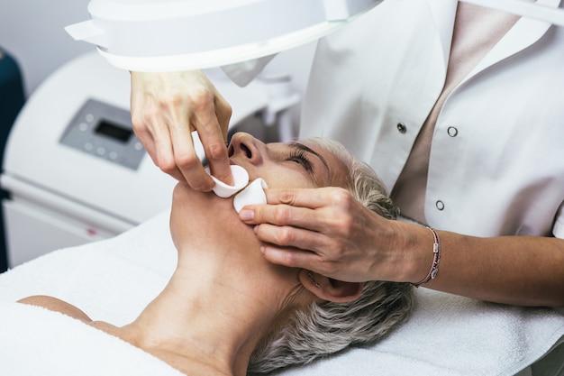 Mitesser-reinigung auf dem gesicht der älteren frau während der gesichtsbehandlung in der luxus-schönheitsklinik.