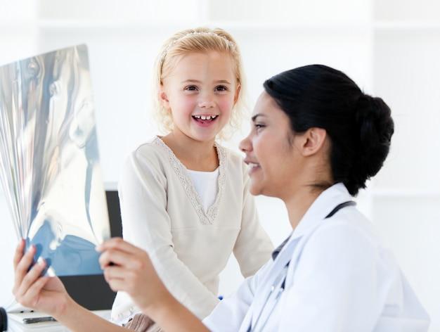 Mitfühlende ärztin, die einem kleinen mädchen einen röntgenstrahl zeigt