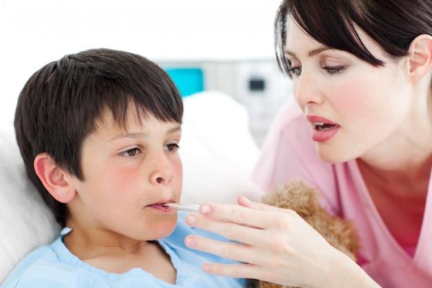 Mitfühlende krankenschwester, die die temperatur ihres patienten nimmt