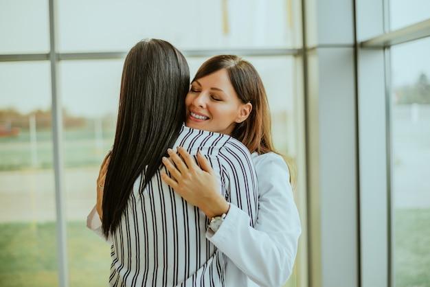 Mitfühlender junger arzt, der patienten umarmt.