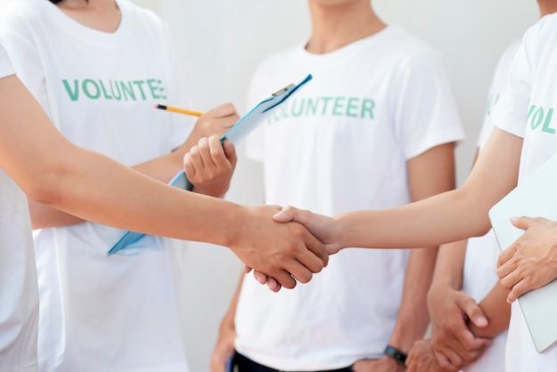 Mitglieder der freiwilligenarbeit, die einen deal abschließen