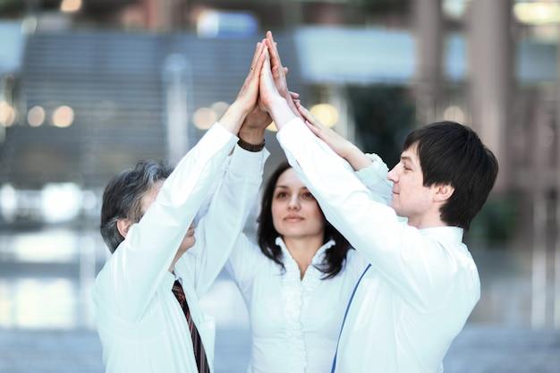 Mitglieder des business-teams geben sich gegenseitig einen high-five und stehen im büro für das konzept der teamarbeit