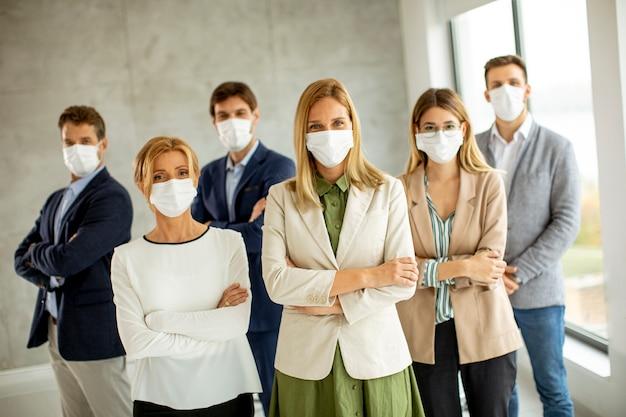 Mitglieder des geschäftsteams stehen mit schützenden gesichtsmasken im büro