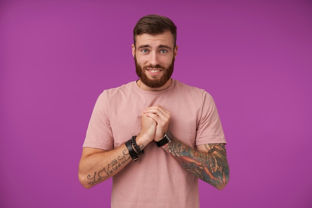Mitleidiger attraktiver brünetter mann mit bart und tätowierungen, die erhobene hände in bettelnder geste falten, stirn runzeln und breit lächeln, isoliert auf lila