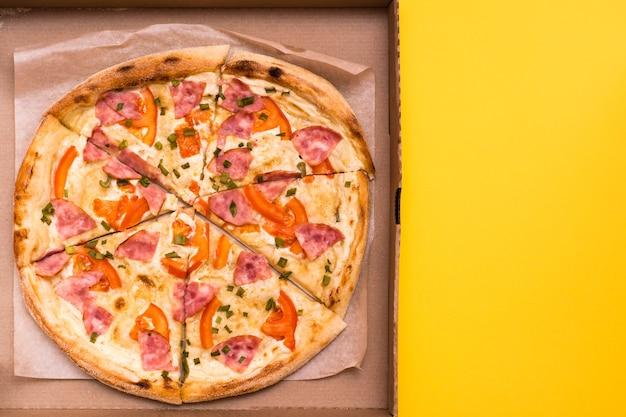 Mitnehmen und lieferung. essfertige pizza im karton auf gelbem grund. speicherplatz kopieren
