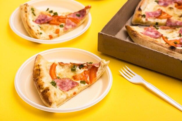 Mitnehmen und lieferung. pizzastück in einwegplastikplatte, pizzaschachtel und gabel auf gelbem hintergrund