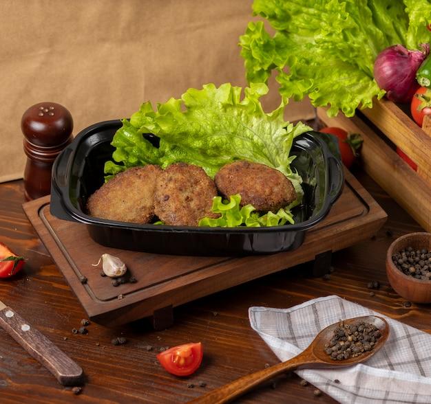 Mitnehmer des rindfleischkoteletts diente mit kopfsalat im schwarzen behälter.