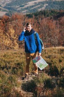 Mitreisender mit karte in der hand und telefon. herbstberge