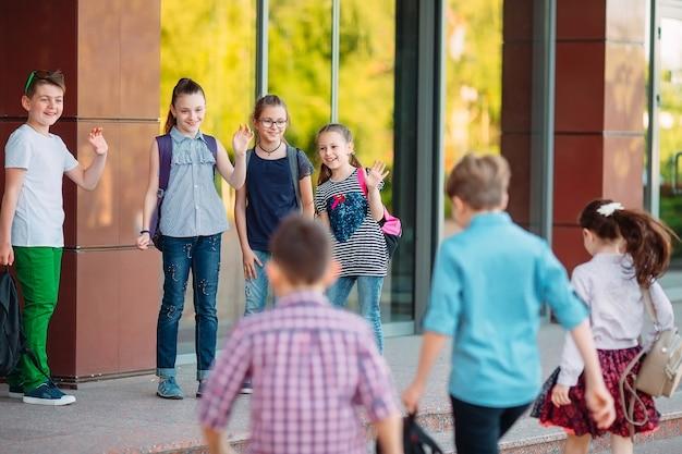 Mitschüler gehen zur schule. die schüler grüßen sich gegenseitig.
