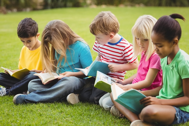 Mitschüler sitzen im gras und lesen bücher