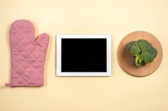 Mitt Ofenhandschuh; digitale Tablette und Brokkoli auf hölzernem Behälter gegen beige Hintergrund