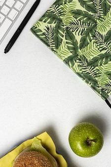 Mittagessen am arbeitsplatz gesundes sandwich nahe laptop auf arbeitstisch. hauptnahrungsmittel für bürokonzept