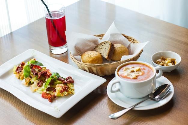 Mittagessen auf dem tisch: tomatenpüreesuppe, salat mit frischem gemüse und sonnengetrockneten tomaten und brot