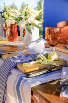 Mittagessen im freien, holzteller, besteck und serviette auf esstisch mit rustikaler und kreolischer dekoration