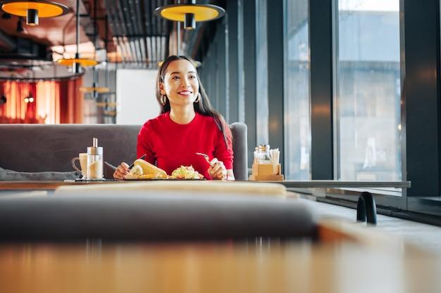 Mittagessen in der kantine. schöne dunkelhaarige geschäftsfrau, die eine pause mit mittagessen in der cafeteria verbringt