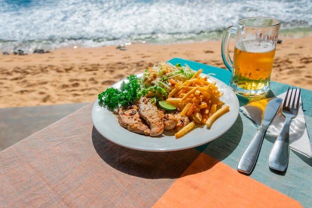 Mittagessen in einem café im freien am meer oder ozean. scheiben von gebratenem fisch und pommes frites mit kohlsalat und einem glas kaltes helles bier
