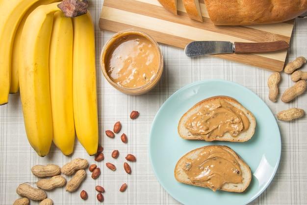 Mittagessen machen, erdnussbutter-sandwich. äpfel, bananen und ein glas milch im hintergrund.