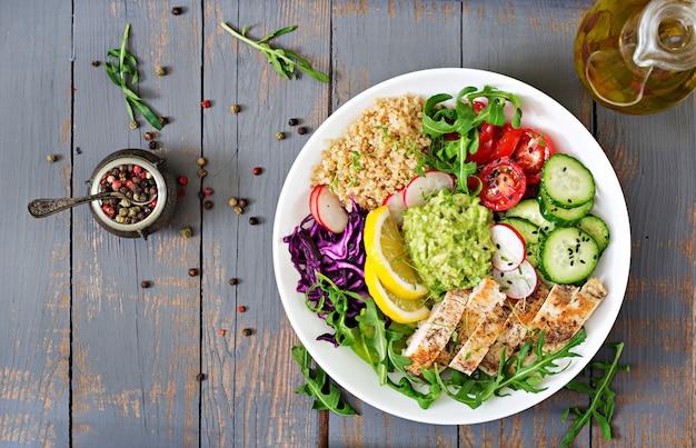 Mittagessen mit gegrilltem hühnchen und quinoa, tomaten, guacamole und rucola. top wetteifern