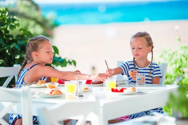Mittagessenszeit. kleine mädchen, die café am im freien mit seeansicht frühstücken