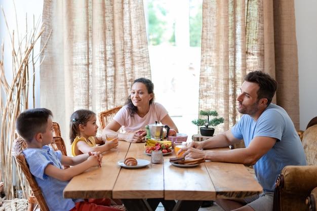 Mittags sitzen zwei eltern und zwei kinder an einem tisch im esszimmer und kommunizieren miteinander