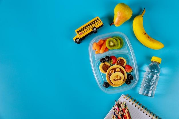 Mittagsbehälter mit pfannkuchen, karotten, birnen und bananen mit schulmaterial. zurück zum schulkonzept.