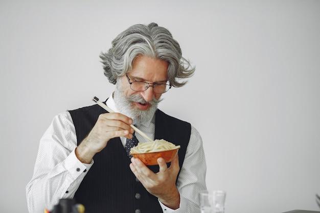 Mittagspause. eleganter mann im amt. geschäftsmann im weißen hemd. der mensch isst nudeln.