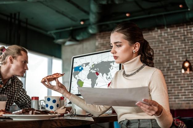 Mittagspause. konzentrierte junge frau, die leckere pizza betrachtet und dokument in der linken hand hält