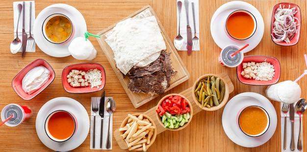 Mittagssetup mit kebab, gemüse, linsen- und tomatensuppen und türkischem meze