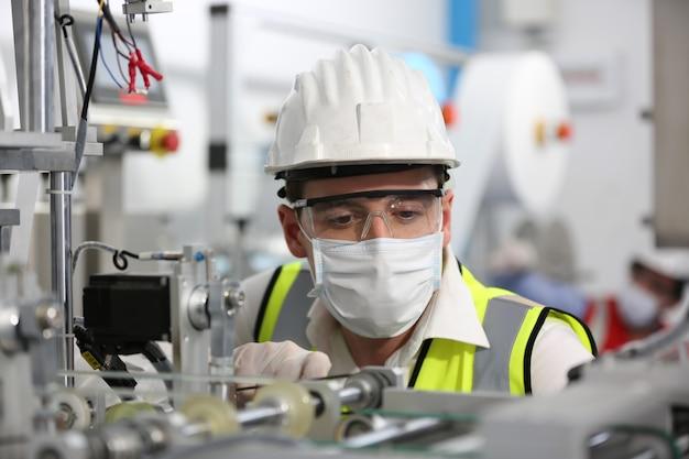 Mitte erwachsener männlicher ingenieure, die maschinenteile auf einer produktionslinie für medizinische masken in einer fabrik untersuchen.