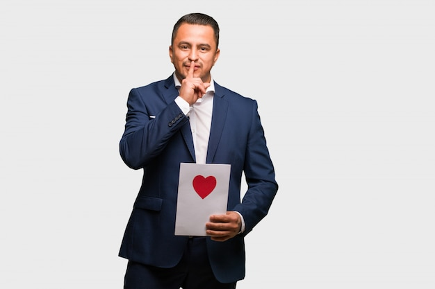 Mitte gealterter lateinischer mann, der den valentinsgrußtag feiert, der ein geheimnis hält oder um ruhe bittet