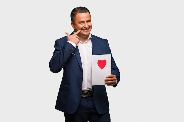 Mitte gealterter lateinischer mann, der valentinsgrußtag feiert, lächelt und zeigt mund