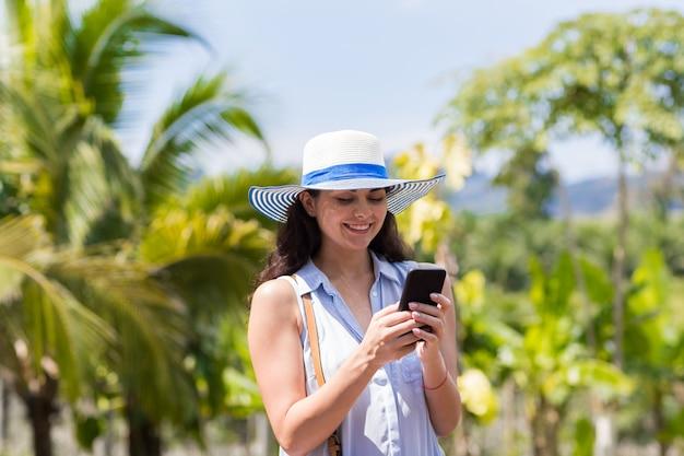 Mitteilung der jungen frau mit zellintelligentem telefon über tropischem wald