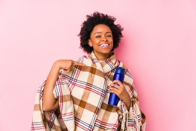 Mittelalter-afroamerikanerfrau in einem kampierenden isolatedsurprised zeigen auf und breit lächelte.