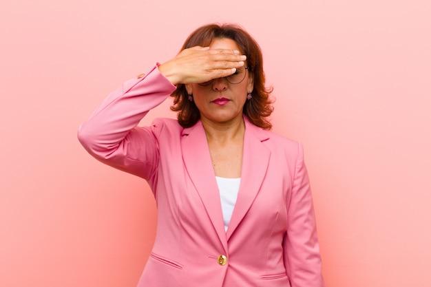 Mittelalterfrau, die augen mit einer hand glaubt erschrocken oder besorgt, sich wundert oder blind auf eine überraschung gegen rosa wand wartet
