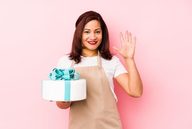 Mittelalterfrau, die einen kuchen auf einer rosafarbenen lächelnden freundlichen darstellenden nr. fünf mit den fingern anhält.