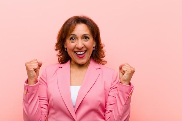 Mittelalterfrau, die entsetzt, aufgeregt und glücklich sich fühlt, erfolg lacht und feiert und wow sagt! gegen rosa wand
