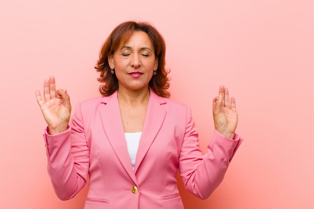 Mittelalterfrau, die konzentriert und meditierend schaut, zufrieden und entspannt sich fühlt und eine wahl gegen rosa wand denkt oder trifft