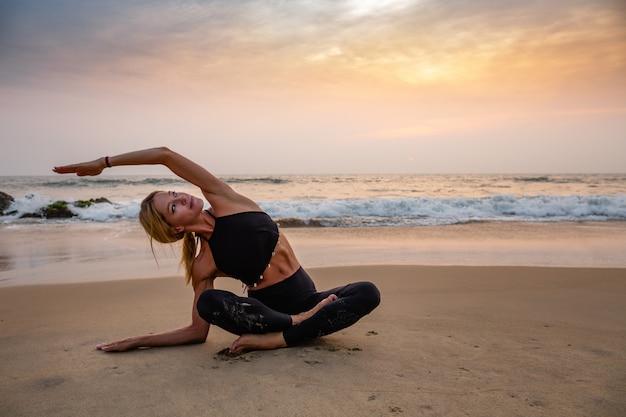 Mittelalterfrau im schwarzen, das yoga auf sandstrand tut