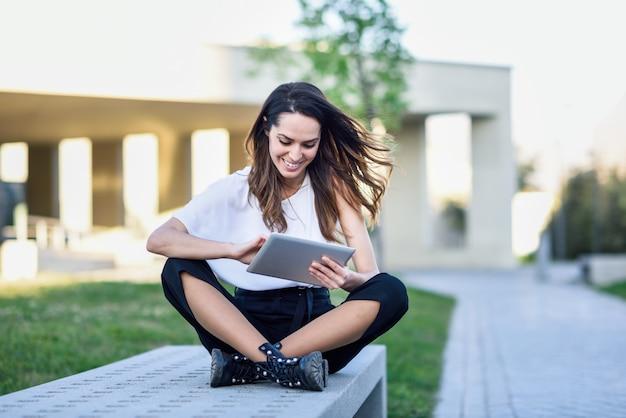 Mittelalterfrau, welche die digitale tablette draußen sitzt im städtischen hintergrund verwendet.