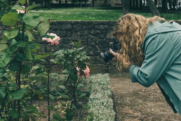Mittelalterfrauenphotograph, der ein fotoschießen mit einer dslr digitalkamera in einem park macht.