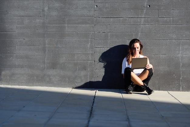 Mittelaltergeschäftsfrau, die mit ihrer laptop-computer sitzt auf dem boden arbeitet.