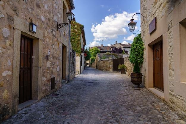 Mittelalterliche altstadt mit steinhäusern, alten türen und fenstern, gepflasterten straßen und malerischer atmosphäre. pedraza, segovia, spanien, europa.