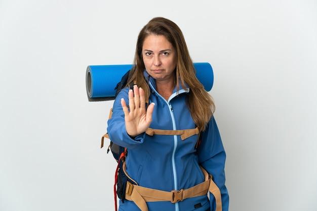 Mittelalterliche bergsteigerfrau mit einem großen rucksack über isolierter wand, die stoppgeste macht