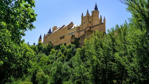 Mittelalterliche burg auf dem berg mit grüner vegetation und blauem himmel