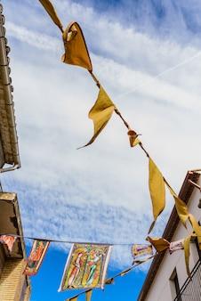 Mittelalterliche fahnen, die zwischen straßen an einem freiluftfestival hängen.
