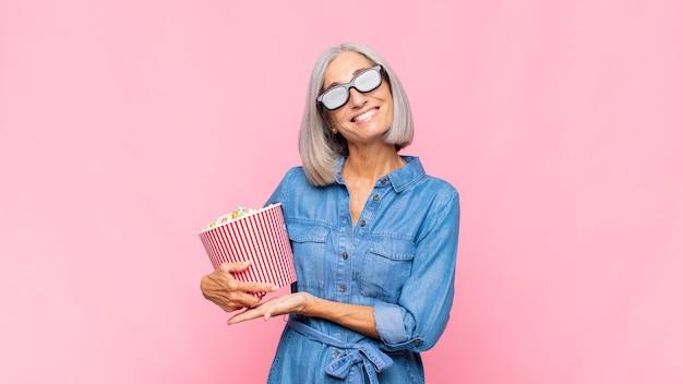 Mittelalterliche frau, die fröhlich lächelt, sich glücklich fühlt und ein konzept im kopierraum mit handflächenfilmkonzept zeigt