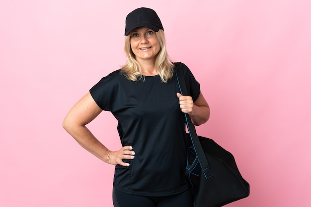 Mittelalterliche frau mit sporttasche lokalisiert auf rosa wand, die mit armen an der hüfte aufwirft und lächelt