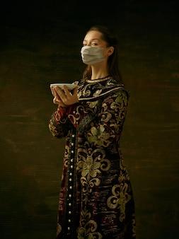 Mittelalterliche junge frau als herzogin mit schutzmaske gegen die ausbreitung des coronavirus